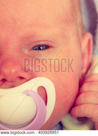 Closeup Of Little Newborn Lying With Teat In Mouth