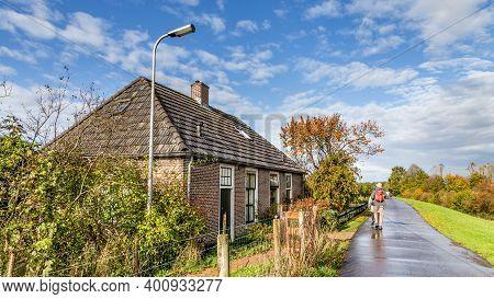 Overijssel, Netherlands - November 2, 2019: Walking Along Traditional Dutch Little Dike Houses Near