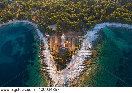 Drone Aerial View Of Lighthouse Tower Of Veli Rat On The Island Of Dugi Otok, Croatia In Early Morni