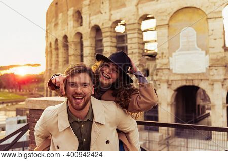 Happy Couple Of Travelers Having Fun, Girl Pointing Forward. Happy Tourists Visiting Famous Monument