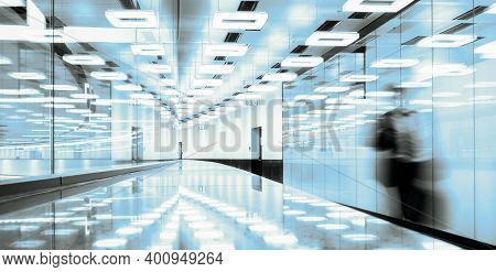 Blurred Silhouette Of A Business Traveler Walking Along Contemporary Illuminated Airport Terminal Ha