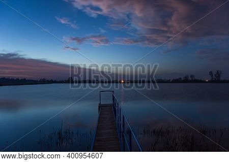Wonderful Colorful Clouds During Sunset Over The Lake With A Footbridge