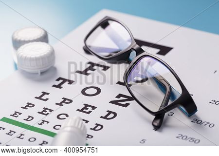 Ophthalmic Accessories Glasses And Lenses With An Eye Test Chart For Vision Correction On A Blue Bac