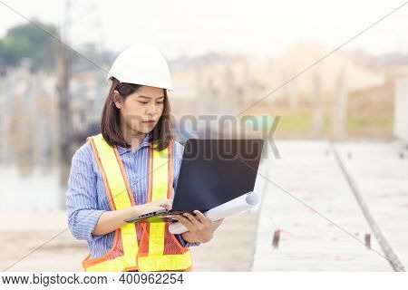 Beautiful Asian Female Engineer In White Safety Hard Hat Using Laptop Computer Notebook Doing Job At