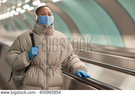 Young Woman In Protective Mask And Gloves Listening To Music While Riding On Escalator At The Airpor