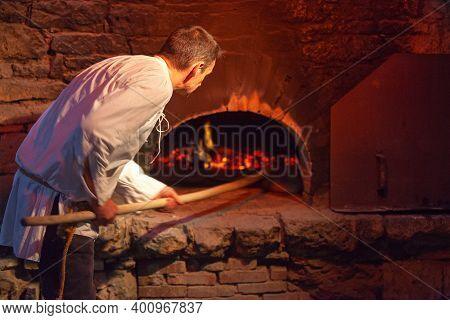 Bazoges-en-pareds, France - July 29 2017: A Medieval Baker Baking The Fouaces, A Round And Airy Brea