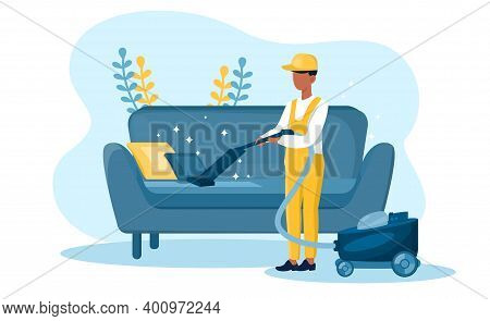 Male Housekeeper In Yellow Overall Vacuum Cleaning Sofa. Janitor With Vacuum Cleaner. Concept Of Jan