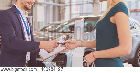 Car Salesman Sells A Car To Happy Customer In Car Dealership And Hands Over The Keys