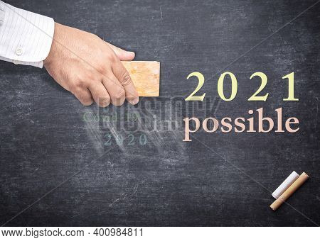Businessman Hand Changing The Word Impossible To Possible. Alphabet I, M, Covid-19, 2020 Being Erase