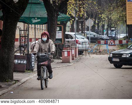 Subotica, Serbia - November 18, 2020: Old Senior Woman Wearing A Respiratory Face Mask Riding A Bicy
