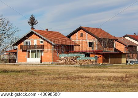 Row Of Newly Built Unfinished Red Brick Family Houses With New Roof Tiles Surrounded With Dry Grass