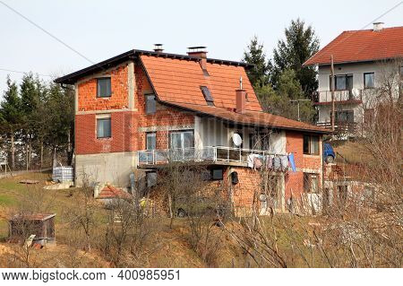 Unfinished Red Building Block Suburban Family House With Large Open Balcony In Front And Unusually S
