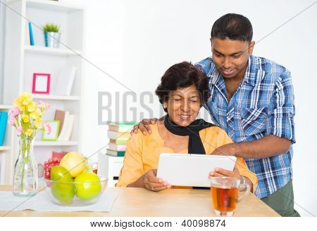 Mature 50s Indian woman and son using digital computer tablet at home