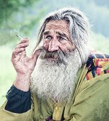 portrait of smoking old man with gray beard poster