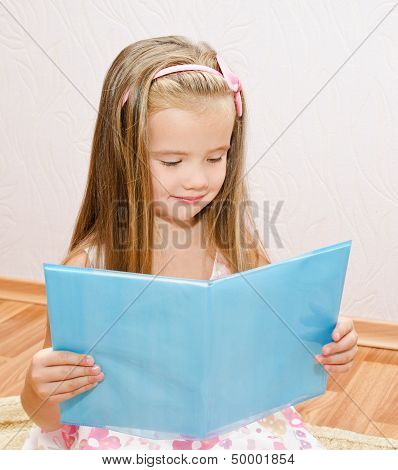 Cute Smiling Little Girl Reading A Book