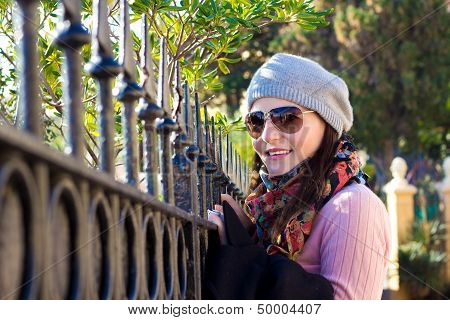 Young Woman Looking Over A Fence And Smiling