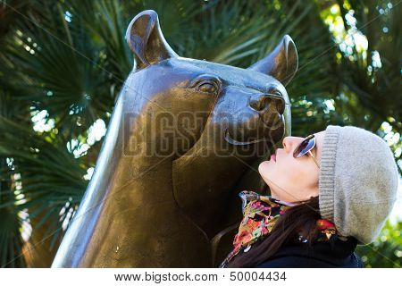 Woman Kissing A Statue Of A  Bear