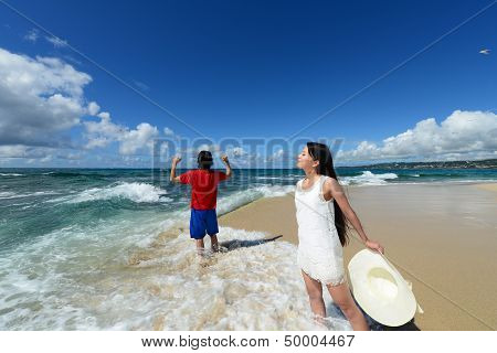 Young man and woman on the beach enjoy sunlight