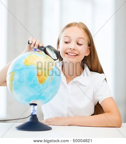 education and school concept - little student girl looking at globe with magnifier at school