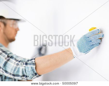 architecture and home renovation concept - male architect measuring wall with flexible ruler