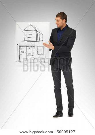 real estate, property, business and accomodation concept - man holding picture with house and blueprint