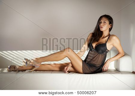 Beautiful and sexy young adult brunette woman wearing black lingerie in sofa