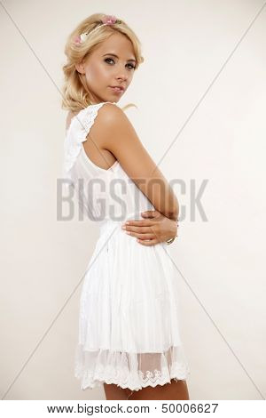 portrait of a beautiful young adult sensuality blonde woman in white elegance dress and flowers in hair isolated on light background