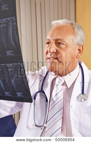 Doctor with x-ray image of human spine in his office