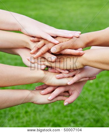Team stacking many hands for motivation in green nature