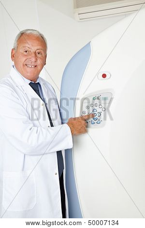 Smiling radiologist doctor pressing button on MRI machine
