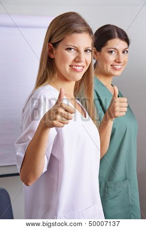 Two happy smiling nurses holding their thumbs up