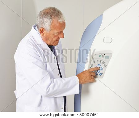 Doctor using buttons of a MRI machine in radiology