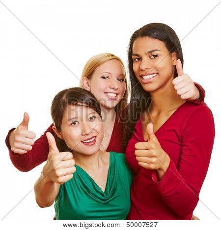 Happy team of three multicultural girls holding the thumbs up