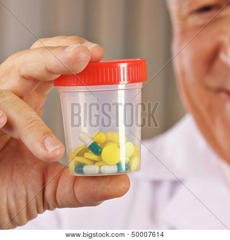 Arzt mit verschiedenen Tabletten in einem Beh���¤lter