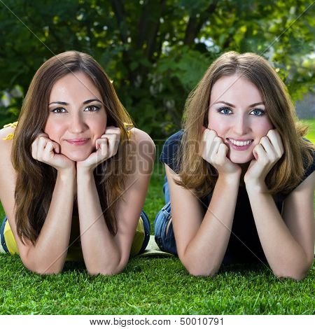 Happy Smiling Young Women Lying On Grass