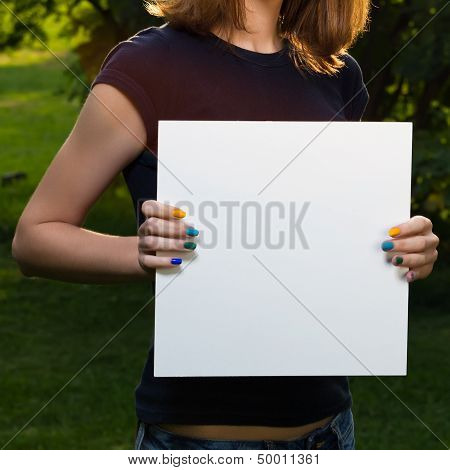 Young Girl Holding White Blank Paper Against Background Of Summer Green Park. Young Girl Showing Bla