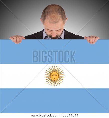 Smiling Businessman Holding A Big Card, Flag Of Argentine