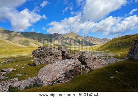 big stones and picturesque hills under blue sky with clouds