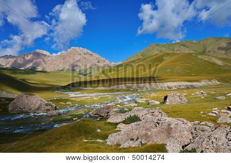 Amazing hills, the small river and blue sky with clouds
