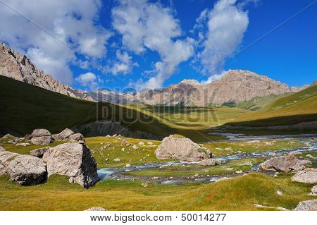 wonderful hills and the big stones under blue sky with clouds