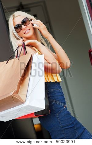 Happy woman with shopping bags calling on the phone