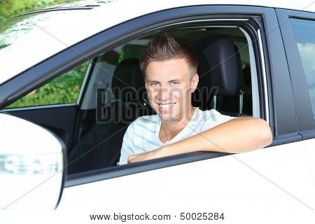 Young man in his new car