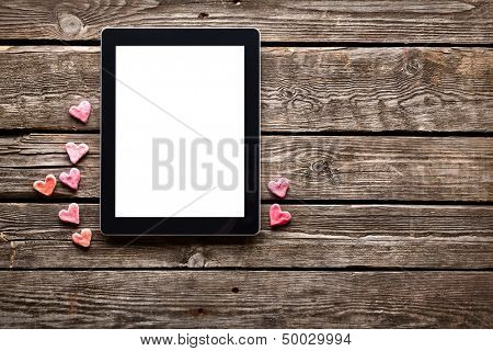 Digital tablet computer with isolated screen and with small red hearts on old wooden desk.