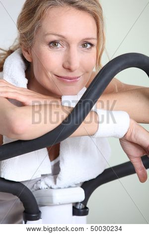 Woman using cycling machine to stay fit