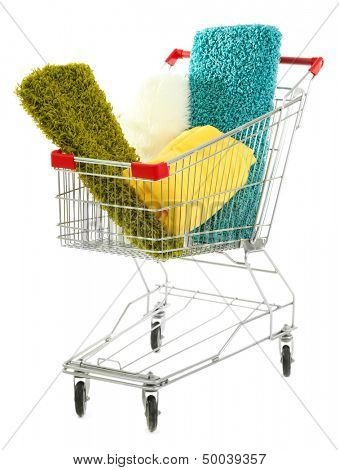 Shopping cart   with colorful carpets and plaids, isolated on white
