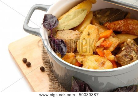 Homemade beef stir fry with vegetables in color pan, on wooden board, isolated on white