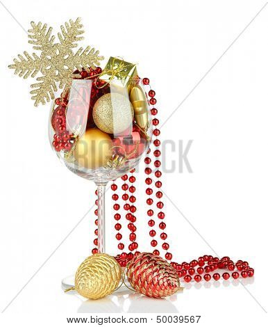 Wine glass filled with christmas decorations, isolated on white
