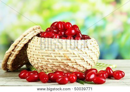 Fresh cornel berries in basket on wooden table