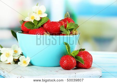 Ripe sweet strawberries in bowl on blue wooden table