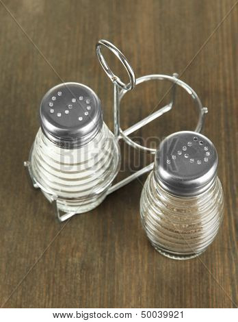 Salt and pepper mills, on wooden background